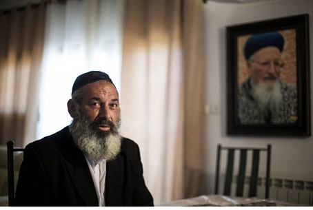 Rabbi Avraham Sinai in front of a picture of former Israeli Chief Rabbi Mordechai Eliyahu