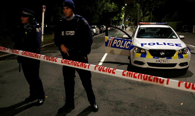 Armed police officers stand guard in outside mosque in Christchurch