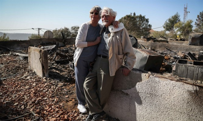 Avigail and husband near ruins of home